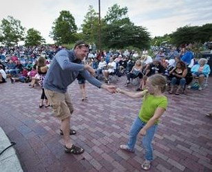 Man dancing with daughter at summer concert at Independence Grove
