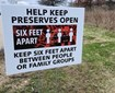 Sign that says Help Keep Preserves Open Stay Six Feet Apart